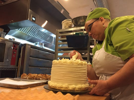 Chroma co-owner Nancy Hauptfleisch puts the finishing touches on a wedding cake inside the bakery.