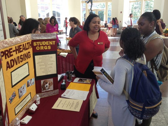 Thesla Berne-Anderson, center, director of pre-college and college outreach at the FSU College of Medicine, explains program options during a reception Friday at the college.