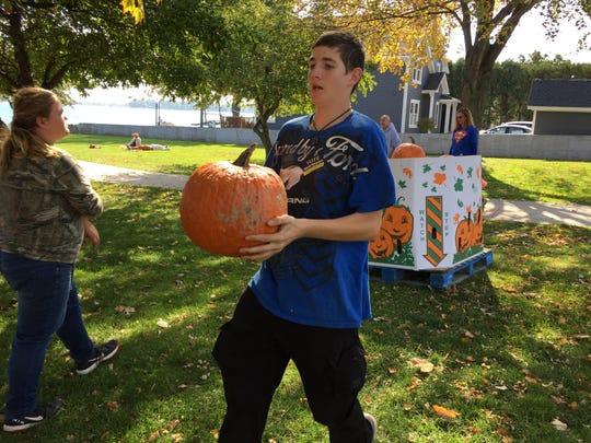 Tyler Burton, of Algonac, carries a pumpkin during the Pumpkins, Politics and Popcorn event.