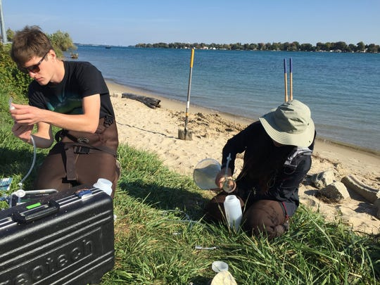 Jack Press and Juan Du check water samples from the St. Clair River.