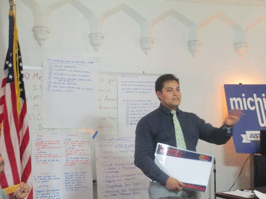 Adonis Flores, with Michigan United, speaks to a class of immigrants about becoming an American citizen, at Michigan United offices in southwest Detroit. On the wall are sentences written by the immigrants about what it means to be American.