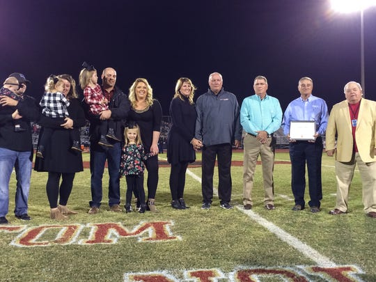 Riverdale Principal Tom Nolan (fourth from right) stands among family and school board members during a ceremony naming Tom Nolan Field Friday.