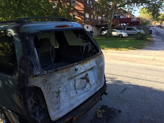 A charred van is parked on Rodman Road in Canby Park. Owner Denise Jenkins believes it was the lone recent car fire in the neighborhood that was unintentionally started.