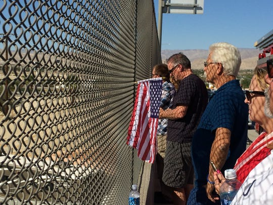"""La Quinta resident Allan Hueberle stands in front of an American flag hanging in a fence on the Interstate 10 interchange at Monterey Avenue. He joined dozens of people waiting for the funeral procession of Palm Springs Police Officer Jose """"Gil"""" Vega."""