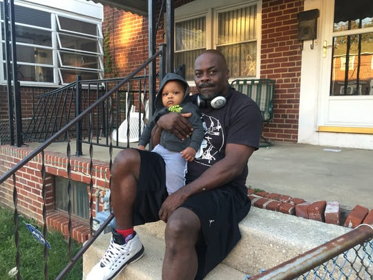 Baaron Williams sits in front of his home on Prospect Road in Canby Park with his 1-year-old grandson on Oct. 12. He said it should not take a tragic fire for people to do something about crime in the community.