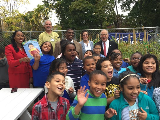 Poughkeepsie City School District Superintendent Nicolé Williams, Director of Food Services David Dunn, Gov. George Clinton School Principal David Scott, Poughkeepsie Farm Project's Jamie Levato and New York State Comptroller Thomas P. DiNapoli pose with third grade students in the Gov. George Clinton School's outdoor garden.