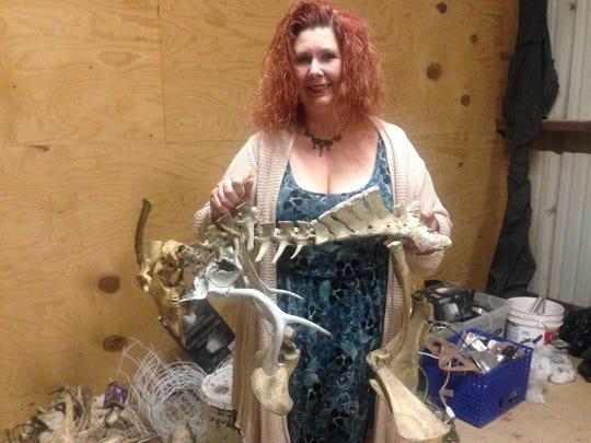 """Artist Mimi Webb holds a """"creature"""" she is in progress of making from the bones of cows."""