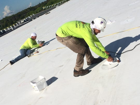 Two Crowther Roofing workers install fasteners by heat welding them to the thermoplastic roof of a warehouse owned by J.J. Taylor Distributing Florida in Fort Myers.