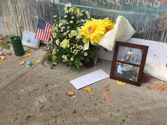 People have left flowers, photographs and notes on a sidewalk near the Before I Die wall to remember Earl Lee Gray, known as Happy, who passed away Tuesday October 25, 2016. Gray was known as the keeper of the wall since it was created in 2014.