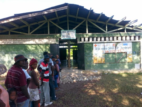 Haitians line up to be treated by medical staff on