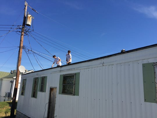 Brothers Ethan (left) and Joshua Ernst, senior and freshman at Riverheads High School, work on re-coating the Jones's roof as part of a Renewing Homes of Greater Augusta volunteer event on Saturday, Oct. 29, 2016, in Verona, Va.