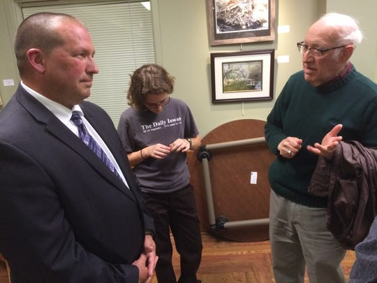 Altoona Police Chief Jody Matherly, left, speaks to community members at an Iowa City police chief finalists meet and greet Thursday night.
