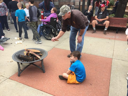 Gary Smithson roasts marshmallows around a fire pit at the Tennessee Veterans Home with his grandson Asa Shelton.