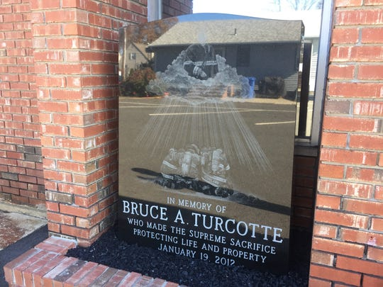 A granite memorial depicting Bruce Turcotte outside of the fire house he dedicated more than three decades of his life to.