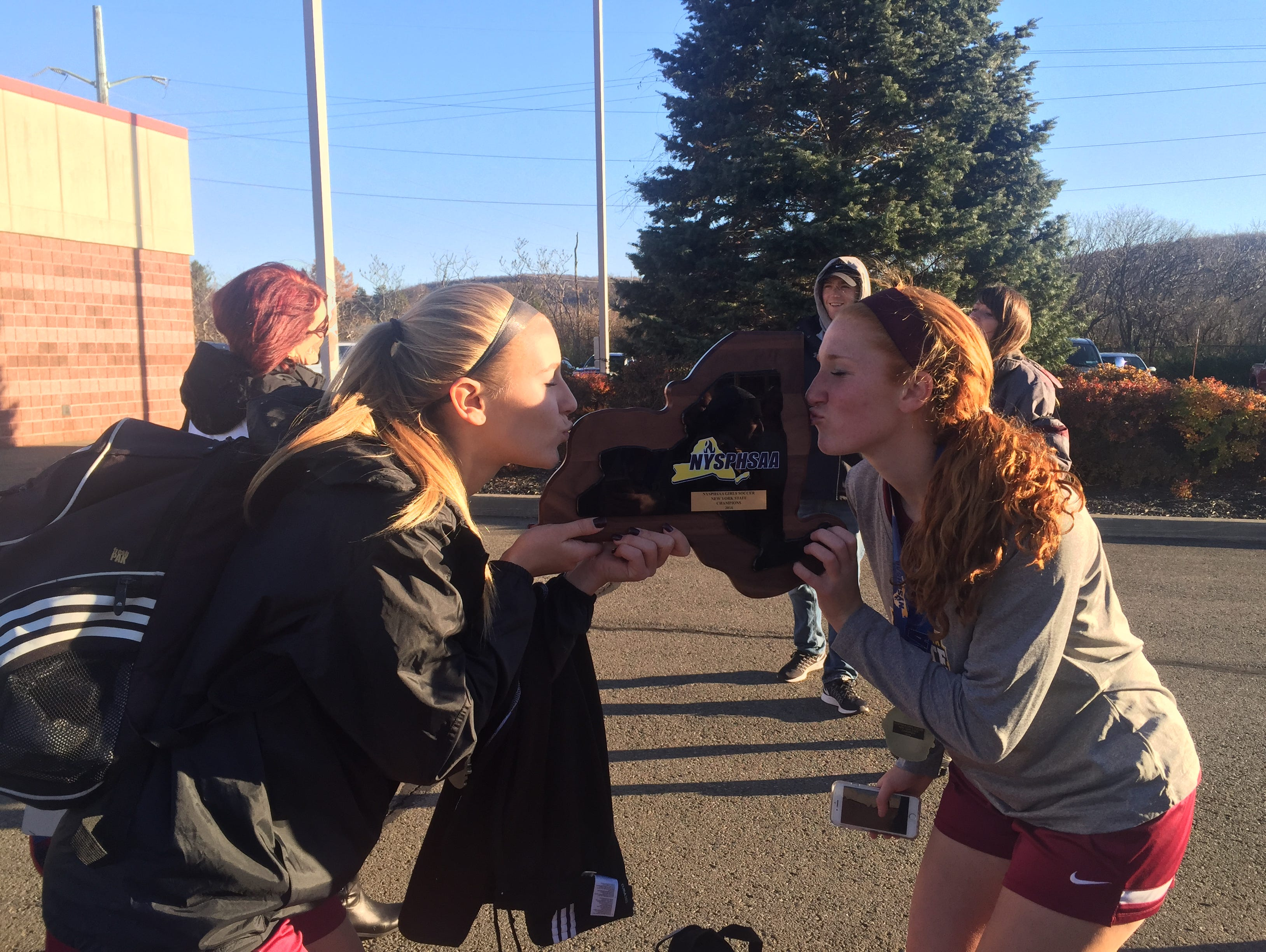 Arlington soccer players Ashley Cross and Abby Carlin kiss the state championship plaque.