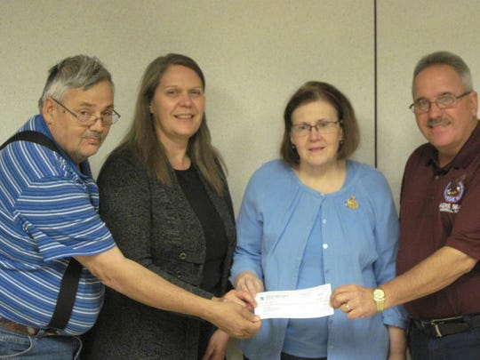 Jerry Leopald, conductor and member of the Eagles' Fair Stand Committee, left, and Bryan Plautz, president of Eagles Aerie 584 and member of the Eagles' Fair Stand Committee, present a check for $100 to Debbie Moellendorf, UW-Extension 4-H Youth Development educator, and Ann Stoeckmann, program coordinator for the 2016-17 After the Bell program.