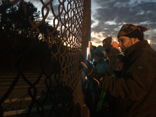 """Participants in a Tuesday protest against the Dakota Access Pipeline look out over Interstate 39 while standing on the Highway 10 bridge in Stevens Point. The protesters held lit signs that read """"Protect Water"""" and """"#NoDAPL."""""""