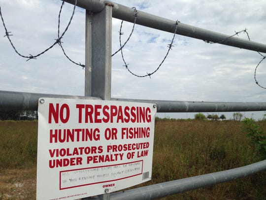 Don't let the barbed wire, a no trespassing sign and