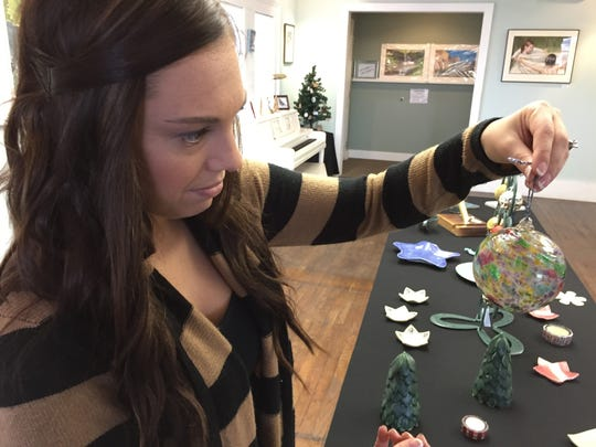 Gina Panoff looks at a handmade blown glass ornament at Studio 1219.