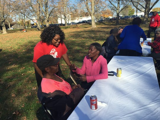 Temeca White (center) speaks with Mary Craig (right) and Shalonda Davis (left) at Wilmington's Day of Thanks & Giving on Saturday.