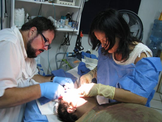 Bryan Buchanan performs oral surgery on a patient in Guatemala. The Wapahani graduate has spent almost 30 years doing mission work in Central America.
