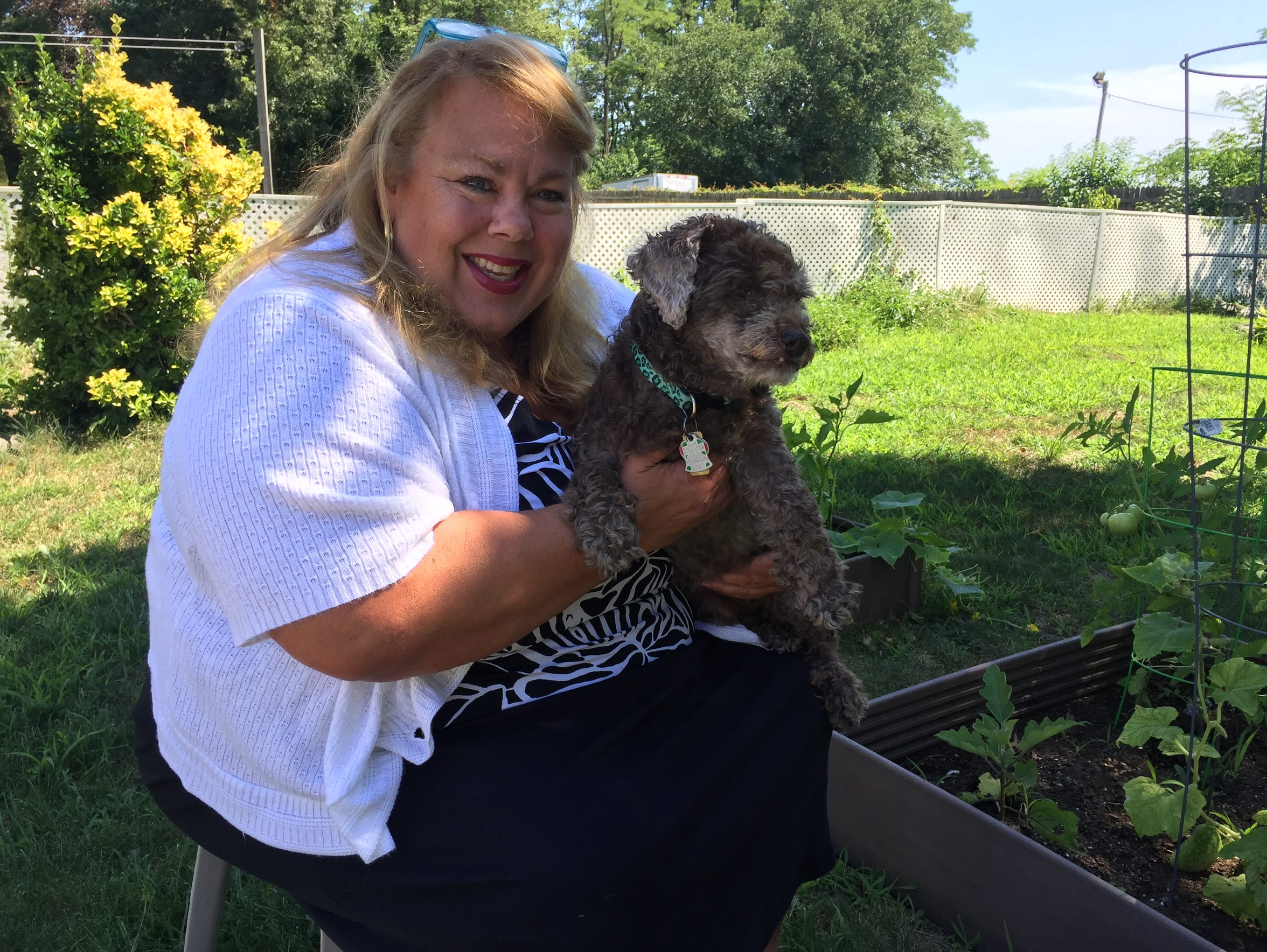 Karen Marsh holds Cricket, one of her two adopted poodles.