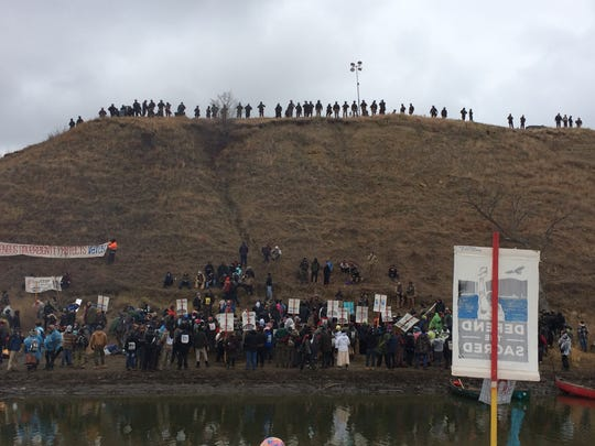 Protesters gather at Standing Rock Reservation on Thanksgiving Day to build a bridge to Turtle Island, which is considered sacred by tribal members. Police line the island hill.