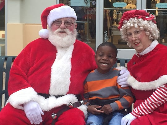 Braylon Baker, 6, poses for a picture with Santa and