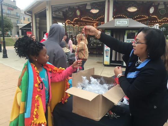 Trinai White, 9, accepts Christmas beads near the Louisiana