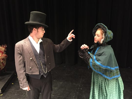 Charity Woman, played by Amelia Modes, asks Scrooge, played by Luke Melville, for donations to help the needy.