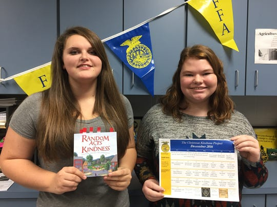 Senior Brooke Shepherd and Junior Emily Kanney, members of the Plymouth High School FFA, pose with the Christmas Kindness Project calendar they created, along with the book that inspired the project.