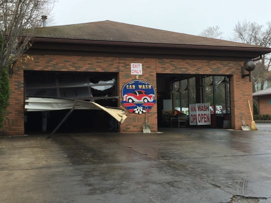 Park Avenue Car Wash garage door damaged Wednesday when a vehicle crashed through it, ending up on church property across Park Avenue West.