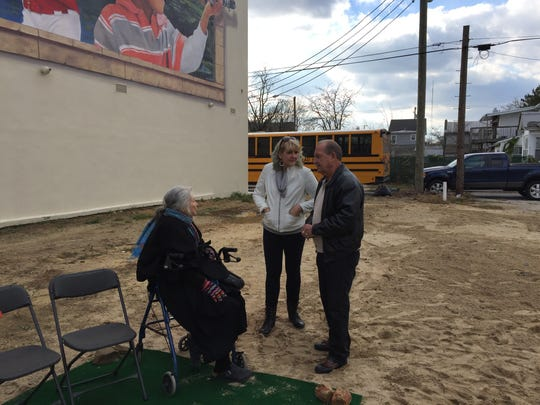 Prior to dedication Thursday of the Gateway Mural, Millville artist Pat Witt (seated) talks with Diane Roberts, executive director of the Riverfront Renaissance Arts Center, and James Parent, Millville Housing Authority commission member.