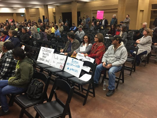 Demonstrator signs at public hearing.