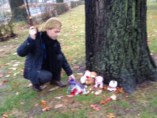 Dennis Rozestwinski lays a bouquet at a tree near the