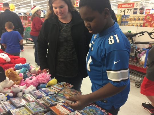 Brandon Hoskins, 10, and his mother Jennifer Hoskins of Howell pick out a DVD to watch for family movie night at the end of Shop with a Cop at the Walmart in Genoa Township. Members of The Well Church donated the DVDs, along with popcorn, candy and toys.