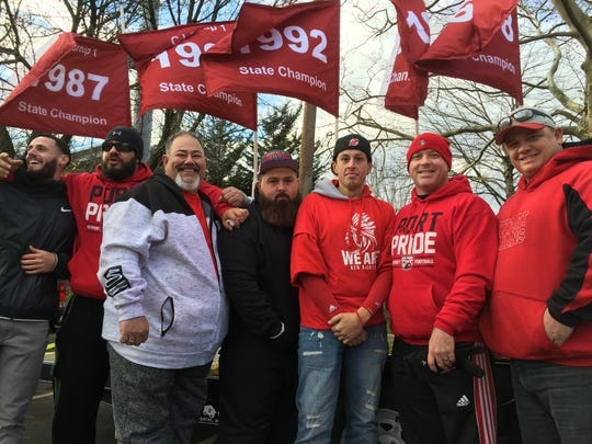 Members of the Keyport Football Alumni Association gathered before Saturday's final. Above them are flags representing the Red Raiders' previous sectional titles.