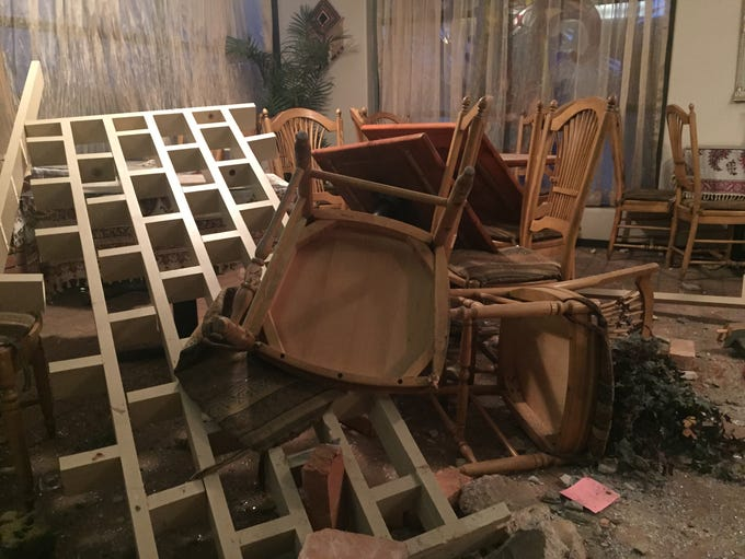 Broken chairs and tables sit in piles on December 3,