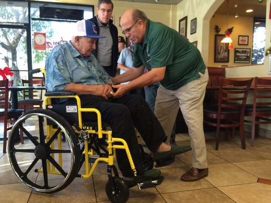 Michael Ohler, right, of Moorpark Knights of Columbus, shows Ventura Fernandez, left, features of his new wheelchair.