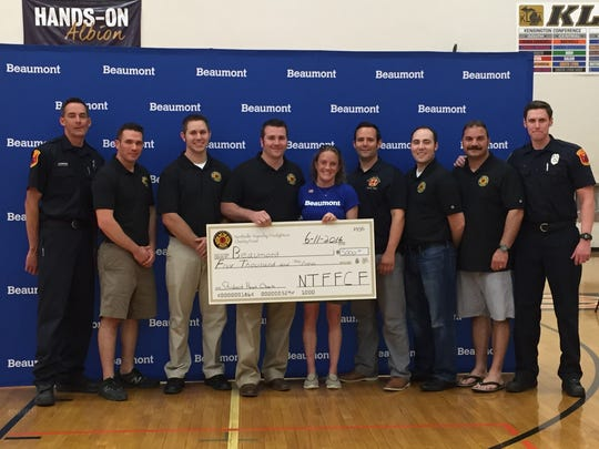 Jennifer Shea, manager, Student Heart Check Program, CMN Beaumont, accepts a donation to the Children's Miracle Network at Beaumont Children's in support of the Student Heart Check Program, from Northville Township firefighters.
