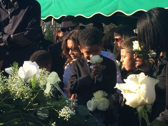 Anthony, 7, clutches a white rose at his father's burial at Mt. Olivet Cemetery in Red Bank Dec. 5, 2016.