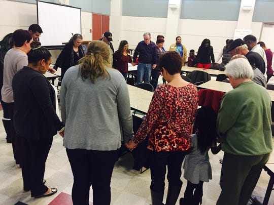 Members of the Forever Club hold hands and pray Dec. 6, 2016. The group met at an ornament-making event to commemorate the deaths of their family members who were homicide victims.
