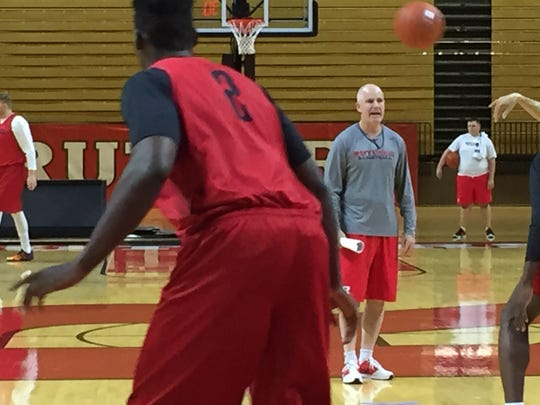 Jay Young (gray shirt) instructs Rutgers' big men during