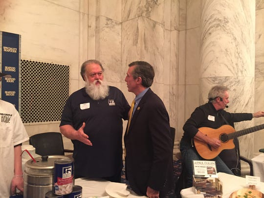 Congressman John Carney, Delaware's next governor, chats with Guy Simmons of SeaWatch International at the Sixth Annual Taste of Delaware . Musician Paul Cullen performs nearby.