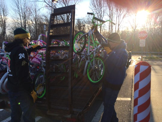 Alan Myers (right) and his son Alan load 100 bikes on their flatbed truck Friday at Walmart in Deptford. The bikes were bought through Pop's Dream, a charity run by Jeff Sanders.