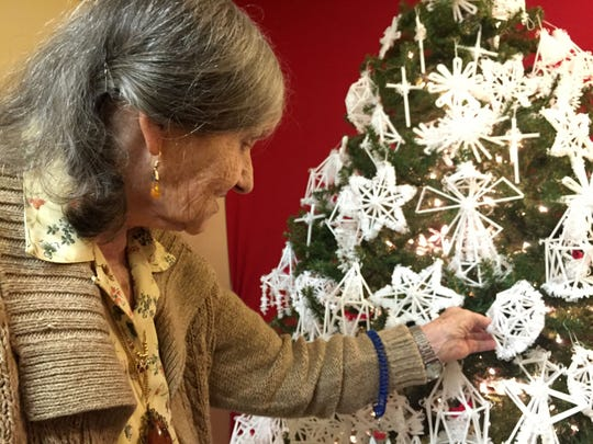 Ann Keraminas, 87, shows off a tree filled with her handmade ornaments at the end of her hallway in an assisted living center in Blount County. Keraminas, originally from Lithuania, is a Holocaust survivor and continues to make traditional straw ornaments she learned to make as a child.