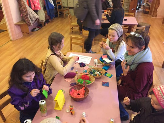 Students work on their crafts in the kindergarten room that was transformed into a crafting station.