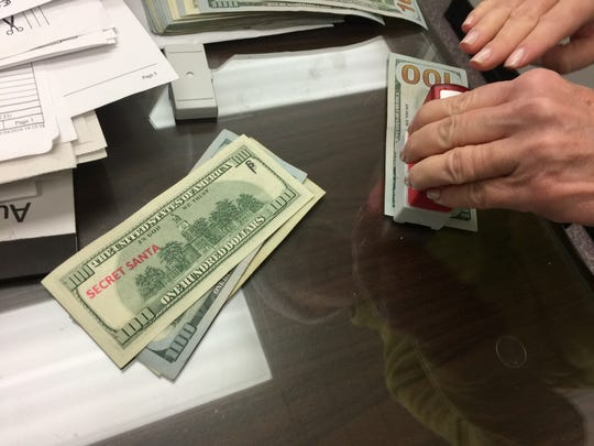 "$100 bills are stamped with ""Secret Santa"" before they're handed out by two Secret Santas who don't want to be identified as they give away $14,000 to people in need on Monday, Dec. 12, 2016."