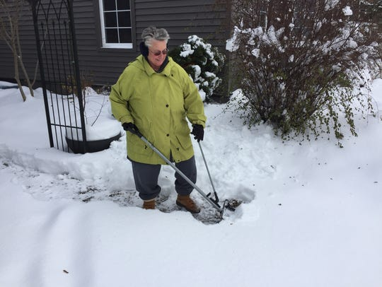 Barbara Swan shovels a path her front door and mailbox