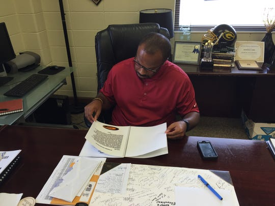 In this 2015 photo, Broderick Fobbs looks over his program manual for the football team.